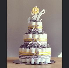 This listing is for a three tier diaper cake with personalized initial cake topper with coordinating flower and chevron ribbon along with your