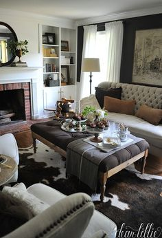 Cozy pillows and throws from HomeGoods add warmth to this den. The cowhide rug helps pull together the dark walls and the lighter sofa and chairs and adds textural interest. (sponsored pin)