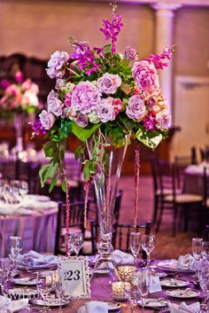 peonies, antique pink roses, dendrobium orchids and amnesia roses arranged on top of a tall clarinet vase with hanging amaranthus