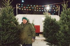 An elderly man posing with a christmas tree on his lot by Stalman & Boniecka