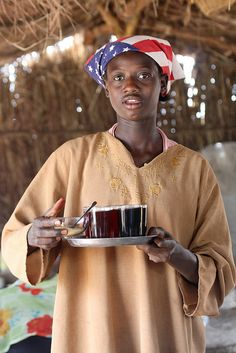 Young girl serving coffee and tea in café in Yida (refugee camp/village in South Sudan for the Nuba people fleeing the air bombing of civilian targets in the Nuba mountains by the Khartoum regime. The Nuba people, however, are admireably resilient and well organized, and have turned the refugee camp into a bustling lovely village in just a few months)    2012 001 South Sudan63 by ngari.norway, via Flickr