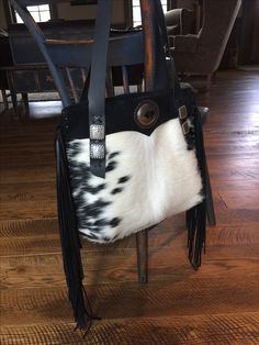 """""""Go West"""" a hair on hide tote with long fringe coming off the sides, a cell phone pocket on the back panel, and lined with two interior pockets. From gowestdesigns.us"""