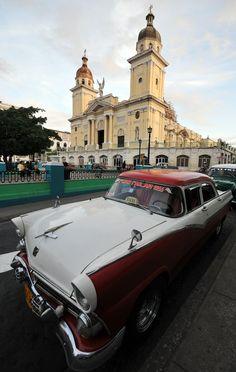 Un viejo auto permanece estacionado en el Parque Céspedes de la ciudad de Santiago de Cuba. Al fondo la catedral de la ciudad