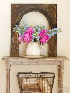 Just one component in a much larger fireplace surround, this cast-iron arch supplies a striking silhouette that captures attention. The arch once likely housed a small door, but now it acts as an art piece that showcases a pretty flower-filled pitcher.