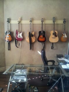 Hang guitars on a strip of wood, and attach to your wall