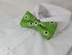 Atomic Bowtie, Nerdy, Geek Fashion, Bow Tie, Science Tie, Adjustable Bow Tie, Teacher Gift, Atom, Physics, Einstein, Genius Gift  • pre-tied bowtie • adjustable under the collar strap • clips in the back with a standard bowtie clip  • standard mens shirt size range (size 14.5- 19.5).   Handmade, made in the USA. NOTE: Each bowtie is cut individually and by hand. The pattern may vary slightly on yours. We do our very best to center designs and make them as symmetrical as possible. All items…