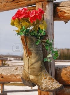 old cowboy boot with artificial flowers on a wooden round pen Stock Photo