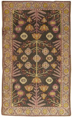 An Indian Agra Rug BB4935 - An Antique Cotton Indian Agra Rug with an unusually modern geometric floral and leaf design rendered invibrant colors on a dark green ...