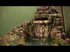 http://www.lizard-landscapes.com/how-to-make-a-waterfall.html  http://www.facebook.com/pages/Lizard-Landscapescom/106440306112510    Learn how to make a rainforest waterfall with this extensive tutorial.  This is primarily intended for reptiles, but you could make this just as an interesting conversation piece for your living room.