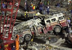 Work crews lift a fire truck from the debris of the collapsed World Trade Center in Lower Manhattan on Saturday evening, September 15, 2001. Hundreds of firefighters who tried to save thousands trapped in the center's two towers following a terrorist attack were still missing in the rubble. (AP Photo/Charles Krupa)