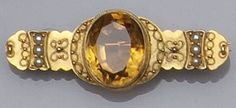 A late Victorian 15ct gold citrine and seed pearl bar brooch The central oval mixed-cut citrine collet set, the bar with trios of seed pearls and applied ropetwist decoration, length 4.5cm.