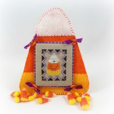 Pinner said: A smiling piece of candy corn has been cross stitched in classic white, orange and gold over dyed embroidery floss and given a fun black and Fall Cross Stitch, Cross Stitch Finishing, Halloween Cross Stitches, Felt Decorations, Purple Ribbon, Candy Corn, Cross Stitching, Embroidery Stitches, Wool Felt