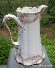 Antique Pitcher Of Theodore Haviland Limoges Schleiger #145    Pattern Is Schleiger #145 On A Gold Trimmed Gently Scalloped And Embossed Melon Ribbed Blank .    Haviland Schleiger #145 is a pattern with a wonderful rose garland design with small pink roses, green leaves and gray shadow foliage. This pattern encircles both the top and bottom of this charming pitcher.    The Gold Trimmed Handle Is Exquisite!  $84.00
