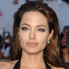 See Birthday Girl Angelina Jolies Beauty Evolution: For the premiere of Mr. and Mrs. Smith, Angelina donned a sexy black leather dress, and amped up the look with a brushed-back hairdo and some serious cat-eye liner.