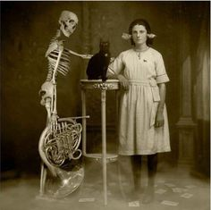 Creepy cat - Vintage photograph of weird woman, black cat and a skeleton holding a tuba