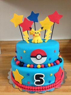 eine zweistöckige blaue pokemon torte für kinder mit gelben blitzen, einem gelben pokemon wesen pikachu, roten, gelben und blauen sternen, pralinen und einem roten pokeball