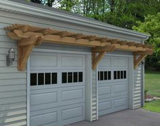 White steel garage doors accentuated with second panel windows and overhead arbor. #pergoladesigns
