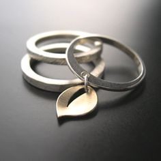 Stackable Rings with 14k Leaf $140.00 3 Sterling Stackable rings can be worn together or individually. Thin band features hand crafted, 14k yellow, dangle leaf. Thicker bands are textured by hammer.