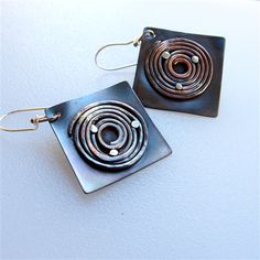 Handmade earrings - copper and sterling silver.  Copper spirals on copper squares with sterling silver rivets imbedded in the spirals to give a cosmic look..  Finished with sterling silver ear wires and black patina than rubbed back to allow some natural copper and silver to show.