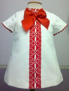 Vestido para bebe niña en pique blanco adornado con encaje de bolillos y piquillo rojo.