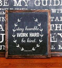 """This hand-painted wood sign offers three wise bits of advice, """"Stay humble, work hard, be kind."""" The text is lettered by hand and framed with a leafy wreath in your choice of background and text colors. The square signage is built and framed in solid wood and distressed to add a rustic touch to any part of your home."""