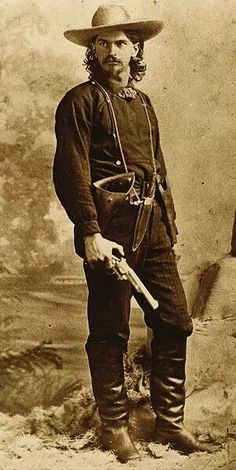 """""""Wild"""" Ben Raymond, with .44 Merwin & Hulbert in one hand and a Smith & Wesson No. 3 New model in his holster. He wears a Bowie knife around his neck. He worked as a mine guard, posed for his photograph in Leadville, Colorado, in 1879, holding a First Model open top Merwin Hulbert Frontier Army revolver. Although the arm is believed to have been a photographer's prop, it nonetheless shows the Merwin's presence in the Wild West."""