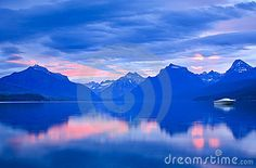 A single boat rests on a calm Lake McDonald surrounded by beautiful sunrise color.