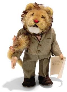 A STEIFF PROTOTYPE MOHAIR LION DRESSED IN SUIT, standing, jointed, golden brown head and tail, brown tipped mane, white mohair chin, brown and black glass eyes, red and black stitching, whiskers, swivel head, pink felt hands, long tail draped over arm, khaki felt suit, blue cotton shirt, pink tie and matching tail ribbon, brown felt shoes, holding paper in left arm and script button with remains of yellow cloth tag, probably 1950s --11¼in. (28.5cm.) high