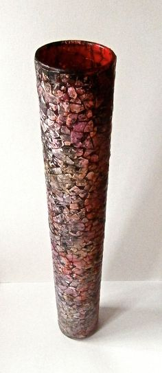This is a glass vase that has been covered in an eggshell mosaic, coloured with ink and treated with a special super strong finish. It is a very unique item.  It measures 16 inches (40 cm ) high x 3 inches (7cm) in diameter.  The red glass column vase was picked up at a charity shop and the eggshells are recycled from breakfast. price 34.00$