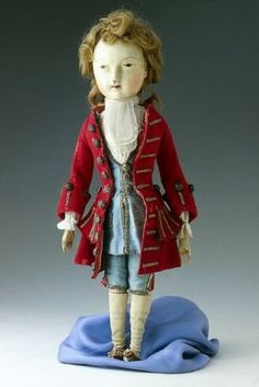 Male doll dressed in blue satin waistcoat and breeches, red wool coat, linen shirt and cravat, silk stockings, leather shoes. English, 1730-40
