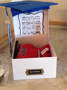 """8th grade graduation keepsake box --white photo box embellished with school color patterned ribbon + school crest (on box lid), """"chalkboard"""" name tag, and scripture verse glued in lid of box (could use poem, inspirational quote, etc.).  If course, the box is topped with a graduation cap in school colors :-)"""