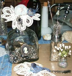 Altered bottle with 3 cameos, hat pins in salt shaker with birdcage on top, tiny flowers in tiny salt shaker & a  bird  nesting in an old silver spoon.
