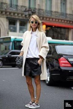 Hellbeige Mantel aus Bouclé, Weißes T-Shirt mit Rundhalsausschnitt, Schwarze Ledershorts, Graue Slip-On Sneakers mit Schottenmuster für Damenmode