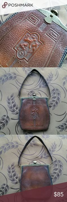 """Antique 1918 Jemco Art Nouveau leather purse Authentic Jemco steer hyde hand tooled purse in the quintessential art nouveau style.  Features gorgeous embossed flower design surrounded by geometric line work. Border is hand stitched with black leather.  Patented 1915-1917  Manufactured July 23, 1918. Mossy green suede interior with small interior pocket Hidden locking mechanism. Locks when  front tab is turned In excellent antique condition,  only one weak point in the handle.  7"""" Width 8""""…"""