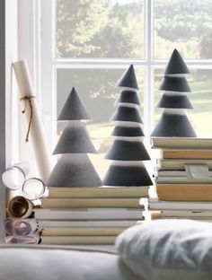 Handmade paper Christmas trees placed on books in the windowsil with a sunny garden scene viewed through the window.