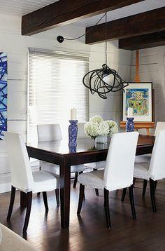 Table en bois, chaises blanches, poutres de bois et lustre noir au dessus de la table