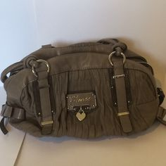 GUESS HANDBAG. AUTHETIC In perfect condition. Never used. This cute Guess purse has two bows on each side with a light purple interior. It's so cute and has plenty of space for your belongings. Definitely recommend Guess Bags Shoulder Bags
