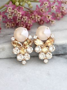 champagne Earrings,Bridal Swarovski Earrings, Bridal Ivory Cream Earrings, Gift For Her, Bridal Rose Gold Cluster Earrings,Ivory Nude Studs Dazzling Post Cluster Crystal earrings feature a Marquise Rivoli and Diamond cut crystals set on a secure prong settings. The perfect shade for cocktail parties or to add a touch of color to your wedding ensemble Petite Delights is an Official SWAROVSKI® Branding Partner Our brand is legally licensed & authorized By Swarovski Company for high quali...