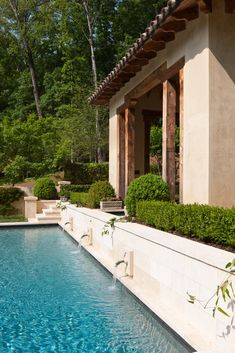 A pool cabana overlooks the back yard amenities in this French-inspired home designed by William T. Baker.