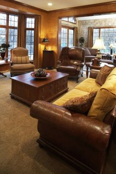 Warm room into another room, with distressed brown leather covered sofa and wing chair, light brown carpet, large dark coffee table. Textured walls & numerous floor to ceiling windows light the large joined living room areas.