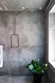 Concrete bathroom with exposed copper pipe shower