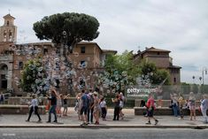 Street performer producing soap bubbles among a group of tourists on the sidewalk on a sunny day in historic Rome.