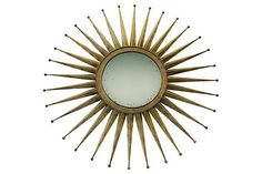 Gold mirror with a sunburst design. Photo taken at a low angle.