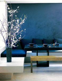 modernes wohnzimmer interior mit wandfarbe blau-sitzecke aus beton mit blauen kissen und moderner esstisch schwarz
