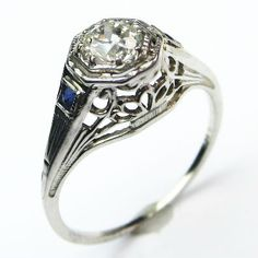 Sweet Sapphire Accent Ring: A pretty ring that delivers lots of sparkle and detail with squares of deep blue sapphires accenting each engraved shoulder. Ca. 1930.  Maloys.com