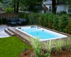 Hydropool Self Cleaning swim spa installed in ground with stone deck