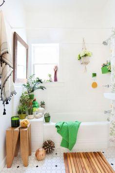 Biała łazienka z zielonymi i drewnianymi dodatkami