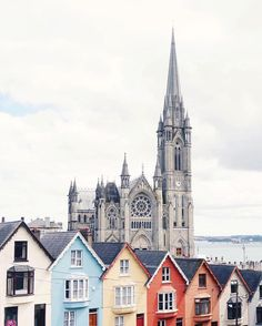 Exploring the small heritage town of Cobh in Cork. In the background of this photo is the grand old Saint Colmans Cathedral. Sitting in front of it are the beautiful old and colourful rowed houses of West View colloquially known by locals as the 'Deck of Cards'
