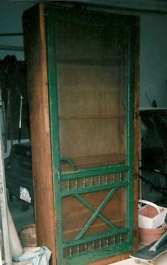 old screen door mounted to book shelves to make sewing storage cabinet