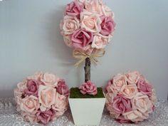 Trio composto de 1 topiaria e 2 bolas de botões de rosa de EVA confeccionadas nas cores rosa claro ou escuro (podemos fazer também em amarelo, champanhe, branco ou vermelho). Utilizamos aproximadamente 30 rosas num tronquinho com laçarote de sisal (que pode ser substituído por fita de cetim) em vaso de MDF branco na topiaria e 24 botões em cada bola (13 x 13 cm). O acabamento é feito com musgo desidratado. <br> <br>Você pode usar como centro de mesa e lembrança para os convidados, mesas de…